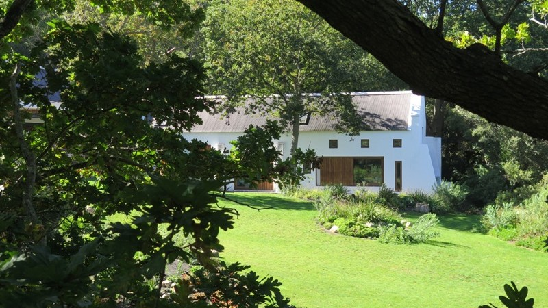 view of the cape dutch farmhouse and rolling lawns